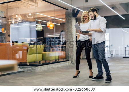 Business colleagues laughing while looking at the laptop