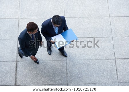 Business colleagues standing outdoors and discussing financial report, view from the top