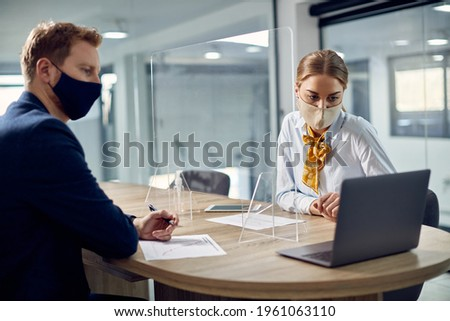 Business colleagues using computer and wearing protective face masks while being separated by protective glass in the office due to coronavirus pandemic. Foto stock ©