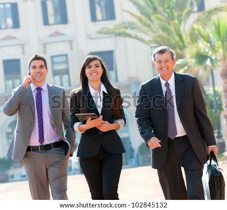 Business colleagues walking outdoors with digital tablet.