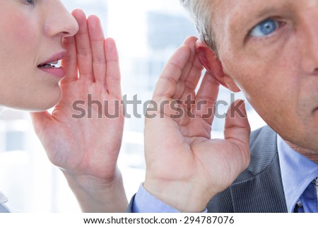 Business colleagues whispering to each other in the office