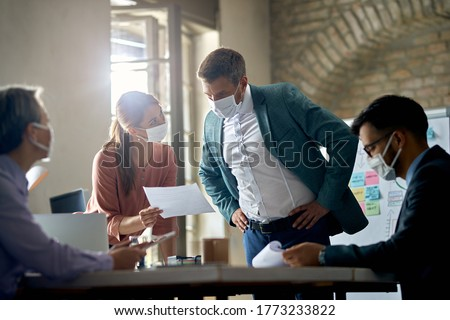 Business colleagues with protective face masks analyzing reports on a meeting in the office.