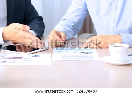 business colleagues working together and analyzing financial figures on a graphs - Shutterstock ID 324598487