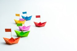 Business competition concept with Colorful paper ships on white background
