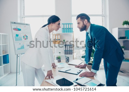 Business competition, side view profile of two colleagues in classy suits having disagreement and conflict, standing in modern work station, place, face to face, lean with hands on the table