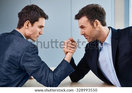 Business competition - two businessman arm wrestling