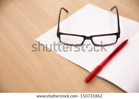 Business composition with laptop glasses and pen over clear pages