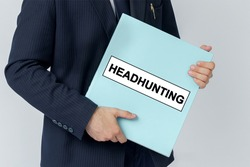 Business concept. A businessman holds a folder with documents, the text on the folder is - HEADHUNTING