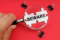 Business concept. A man looks through a magnifying glass at puzzles with the inscription - BEWARE