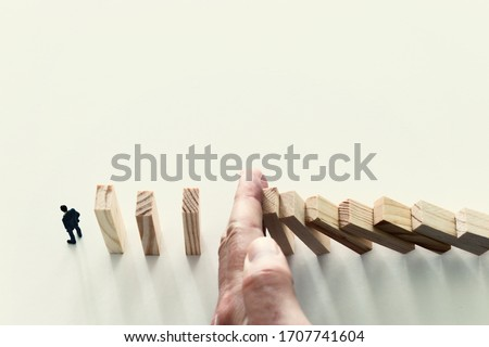 business concept. A man stands near dominoes and unaware of the danger of their fall. risk control and managment idea Foto stock ©