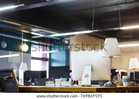 Business concept. An empty office is waiting for employees. Wooden table with computers, lamps, coffee mugs and stationery. Co-working