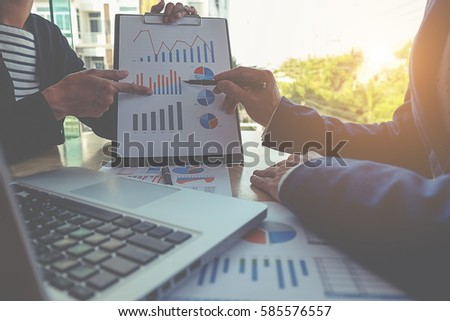 Business concept. Business people discussing the charts and graphs showing the results of their successful teamwork. Selective focus.