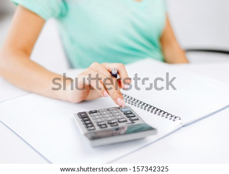 business concept - businesswoman working with calculator in office