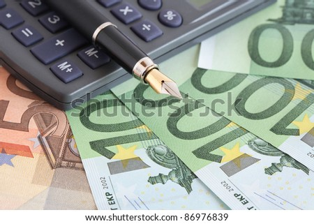 Business concept. Closeup of fountain pen and calculator on european currency background - stock photo