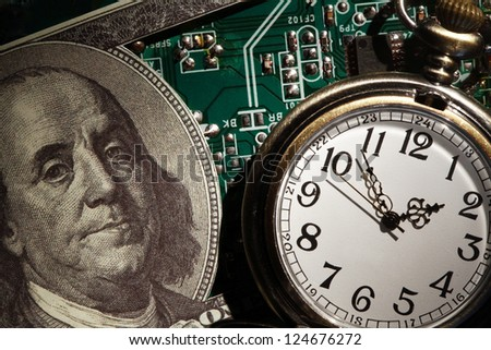 Business concept. Closeup of one hundred dollar note near watch on green computer motherboard