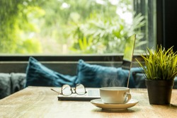 Business concept coffee cup with laptop and eyeglasses on wooden table.