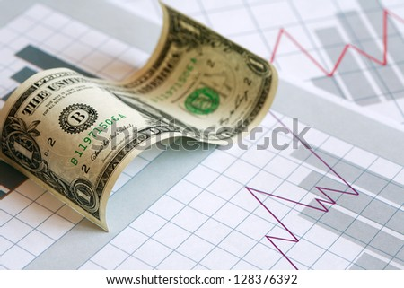 Business concept. Curved one dollar bill on paper background with business chart