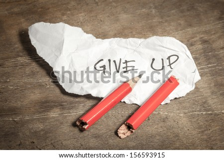 Business concept display wording 'Give up' on crumpled paper with red broken pencil