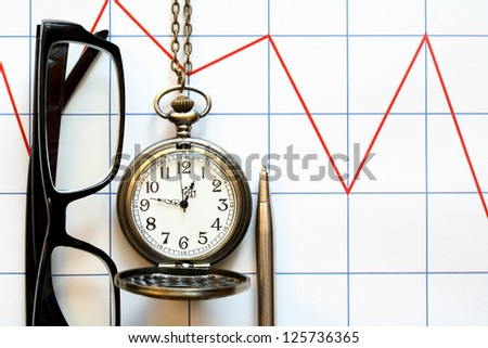 Business concept. Eyeglasses near pocket watch and pen on paper background with red chart
