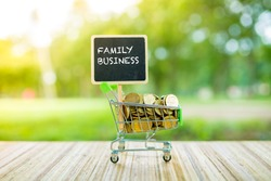 Business Concept : FAMILY BUSINESS word on black board with coins in small container over blur  and sunlight background.