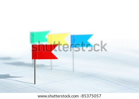 Business concept.Few color plastic flag pins on graph paper background with free space for text