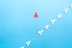 Business concept for innovation and solution with group of white paper plane in one direction and one red paper plane pointing in different way on blue background.