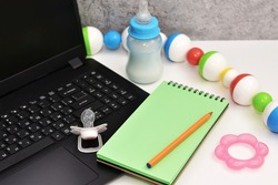 Business concept for the leave of absence for an expectant or new mother Trendy.  Pacifier on the laptop and baby bottle.  Working in a decree. Maternity leave concept.