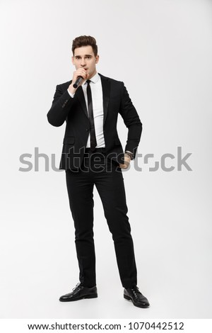 Business Concept: Full-length Portrait young man in black suit is holding a microphone, singing and posing against a white background