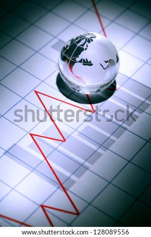Business concept. Glass globe on paper background with chart