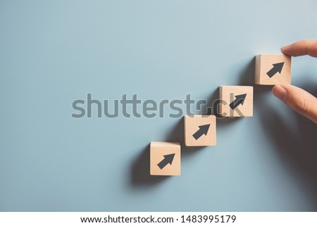 Business concept growth success process, Close up Woman hand arranging wood block stacking as step stair on paper blue background, copy space.