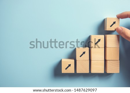 Business concept growth success process, Close up Woman hand arranging wood block stacking as step stair on paper blue background, copy space. Stock foto ©