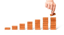 Business concept growth success process - Hand adding brick stacking as step stair on white background, including clipping path