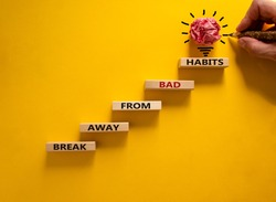 Business concept growth success process. Wood blocks stacking as step stair on yellow background, copy space. Male hand with pencil. Words 'break away from bad habits'. Copy space.