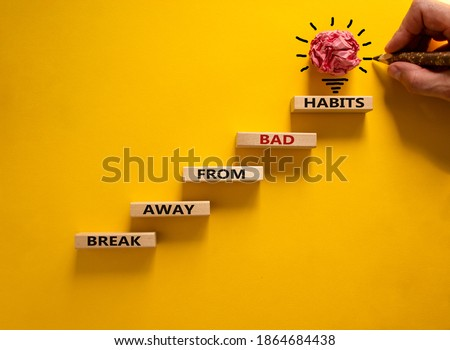 Business concept growth success process. Wood blocks stacking as step stair on yellow background, copy space. Male hand with pencil. Words 'break away from bad habits'. Copy space. Stockfoto ©