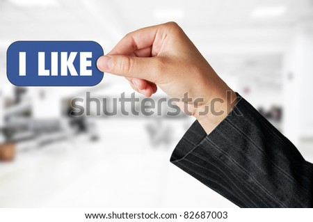 "Business concept: Hand holding an ""I LIKE"" label"