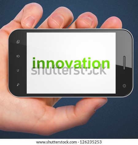 Business concept: hand holding smartphone with word Innovation on display. Generic mobile smart phone in hand on Dark Blue background. - stock photo
