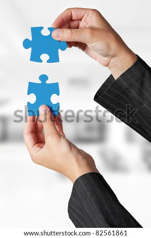 Business concept: Hand holding two pieces of a puzzle