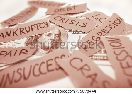 Business concept image. Dollar bank-note laying with peaces of paper with inscriptions. Bankruptcy, crisis, regression, failure in business concept. Focus on franklin eyes. Red colored image.