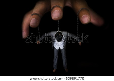 Business concept image of a businessman being controlled by puppet master with chain on neck , arm on black background with black shadow