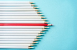 Business concept - lot of white pencils and one color pencil on blue paper background. It's symbol of leadership, teamwork, united and communication.