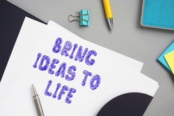 Business concept meaning BRING IDEAS TO LIFE with inscription on the piece of paper.