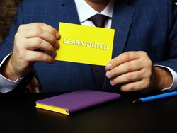 Business concept meaning LEARN DUTCH with sign on the piece of paper. Motivation concept calling learning DUTCH language