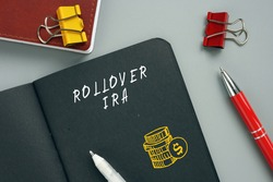 Business concept meaning ROLLOVER IRA Individual Retirement Accounts with sign on the sheet. A rollover IRA  is a transfer of funds from a retirement account into a traditional or a Roth  IRA