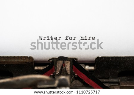 Business concept, message Writer for hire typed by a vintage typewriter on white paper. Red and black ribbon is visible on the machine. Concepts of journalism, author, copywriter, tradition, honesty