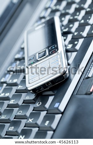 Business concept - mobile phone over laptop keyboard