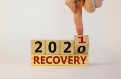 Business concept of new year 2021 recovery. Male hand flips a wooden cube and changes the inscription 'recovery 2020' to 'recovery 2021'. Beautiful white background, copy space. Recovery 2021 symbol.
