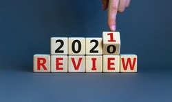 Business concept of planning 2021. Male hand flips a wooden cube and changes the inscription 'Review 2020' to 'Review 2021'. Beautiful grey background, copy space.