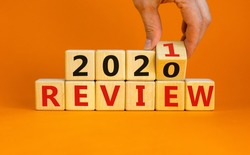 Business concept of planning 2021. Male hand flips a wooden cube and changes the inscription 'Review 2020' to 'Review 2021'. Beautiful orange background, copy space.