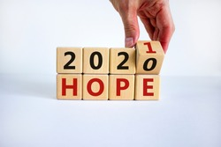 Business concept of planning 2021. Male hand flips a wooden cube and changes the inscription 'Hopes 2020' to 'Hopes 2021'. Beautiful white background, copy space.