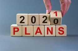 Business concept of planning 2021. Male hand flips wooden cube and change the inscription 'Plans 2020' to 'Plans 2021'. Beautiful grey background, copy space.